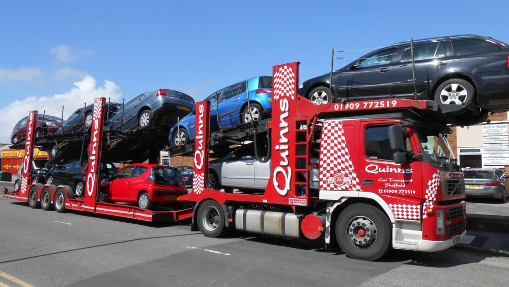 Car transporter in sunshine carrying multiple cars